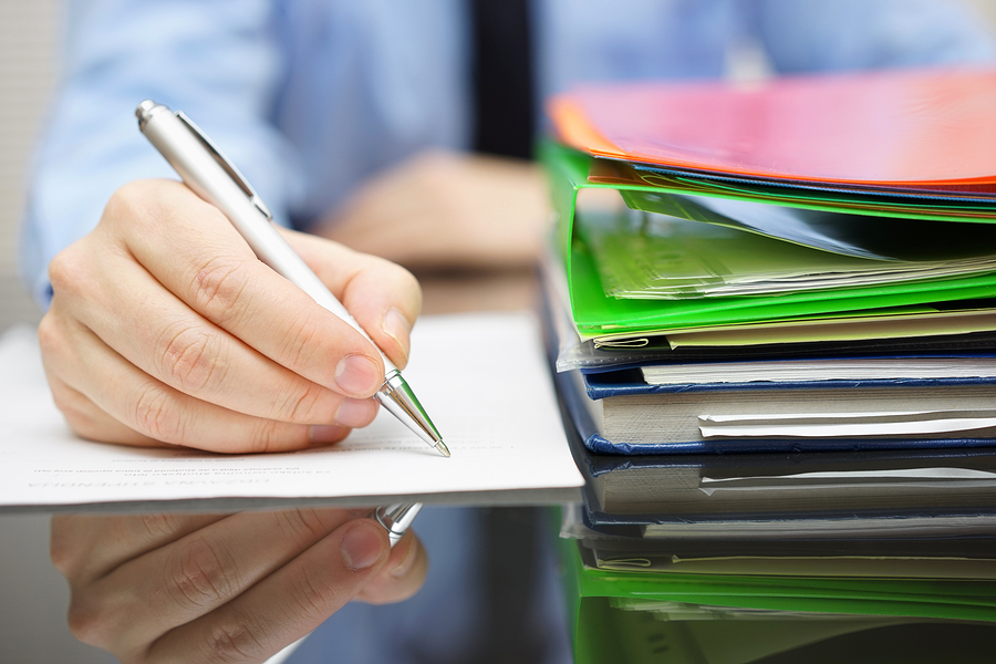 A businessperson takes notes and reviews a stack of documents in a folder.